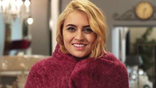 Das glückliche Mädchen wickelt sich selbst in eine Decke