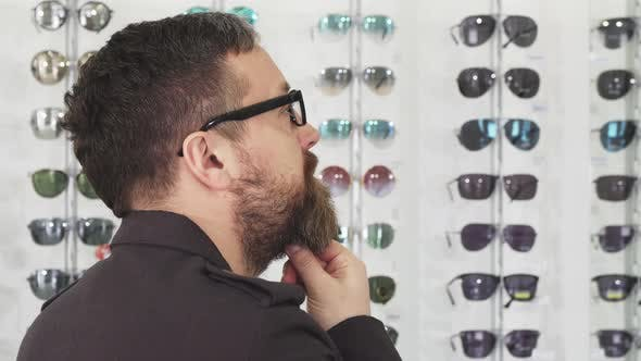Thumbnail for Shot of a Dountful Man Choosing Sunglasses at the Shop