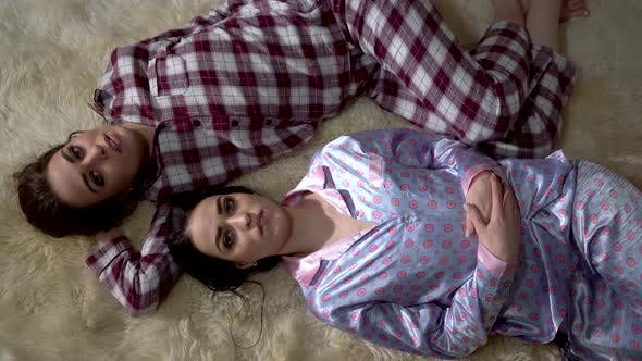 Thumbnail for Two Sisters Twins in Pajamas Lie on the Soft Carpet