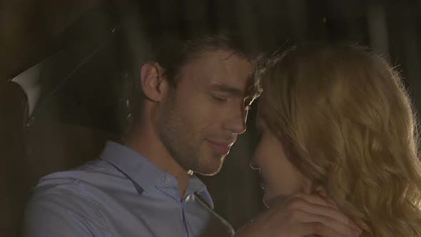 Thumbnail for Handsome man looking passionately at blond woman, caressing gently, rainy night