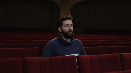 Man Watching a Theater Performance Alone