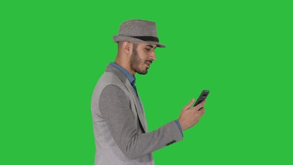 Thumbnail for Man walking with a phone and serfing internet on a Green