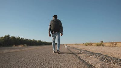 Man walks on the side of a road