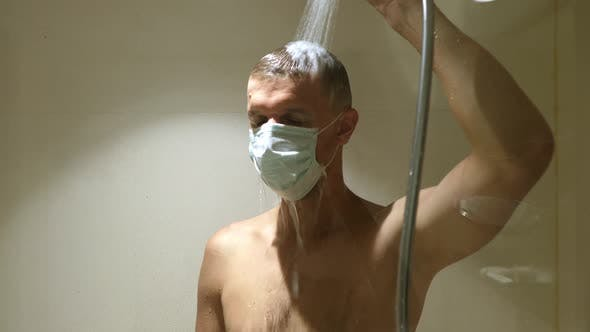Depressiver und frustrierter Mann in Gesichtsmaske unter der Dusche mit Gesichtsmaske