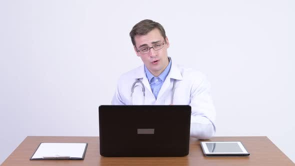 Cover Image for Young Happy Handsome Man Doctor Explaining Something Against Wooden Table