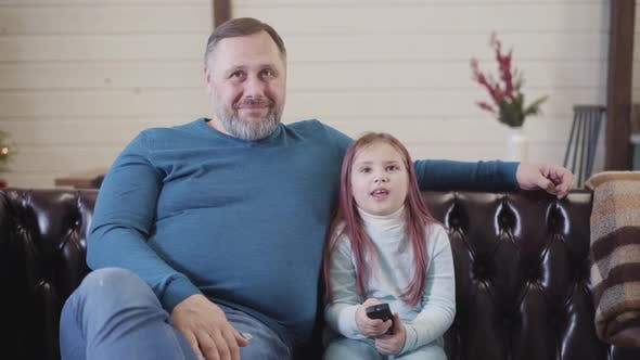 Thumbnail for Happy Daughter Watching TV with Father and Talking. Portrait of Joyful Caucasian Girl and Man