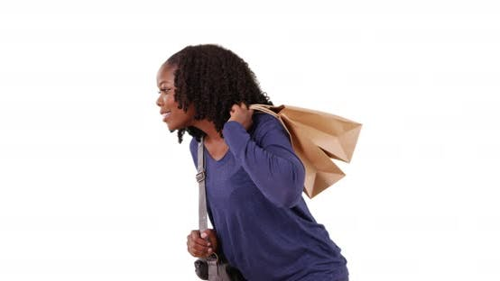 Thumbnail for Black female carrying shopping bags walks over to look at something in studio
