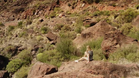 Young Woman Sitting on a Boulder in the Valley