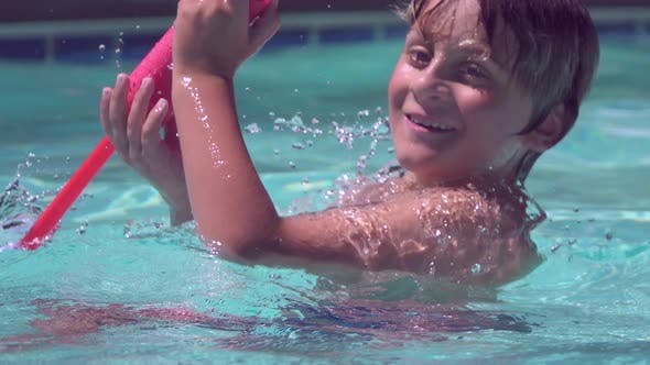 A boy plays in a pool at a hotel resort.