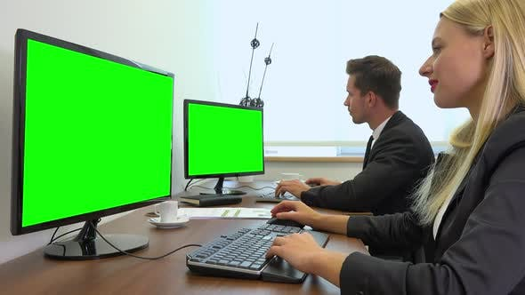 Thumbnail for Two office workers, man and woman, work on computers with green screens and talk