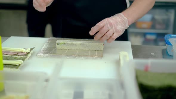 Cook Prepares Japanese Rolls Using a Mat