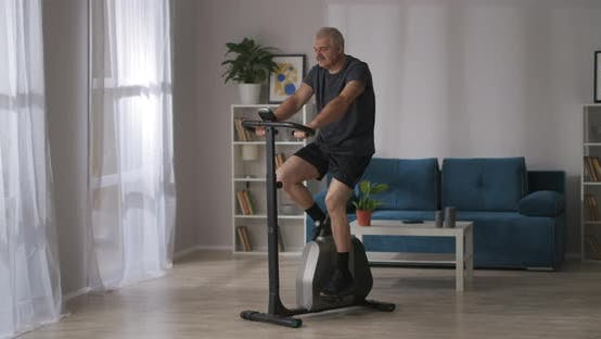 Healthy Lifestyle in Middle Age Man Is Training on Stationary Bicycle in Room Keeping Good Physical