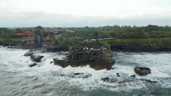 Empty Tanah Lot Temple on Dark Rocky Cliff at Sea During Dangerous Weather