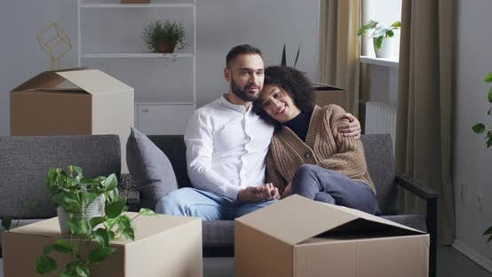 Thumbnail for Young Interracial Multiracial Couple Family Surrounded By Boxes and Houseplants Sitting on Sofa