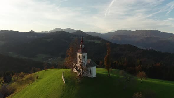 Thumbnail for Aerial View of Hills, Colorful Forest and Sv Tomaz Church. Sunset in Slovenia in Autumn