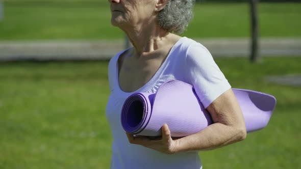 Thumbnail for Side View of Woman Walking in Park, Holding Yoga Mat in Hand