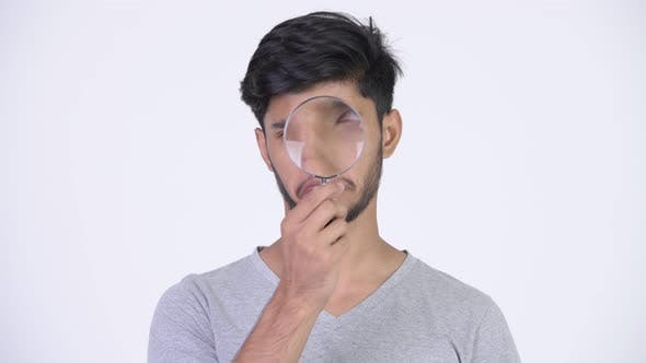 Thumbnail for Young Handsome Bearded Indian Man Playing with Magnifying Glass