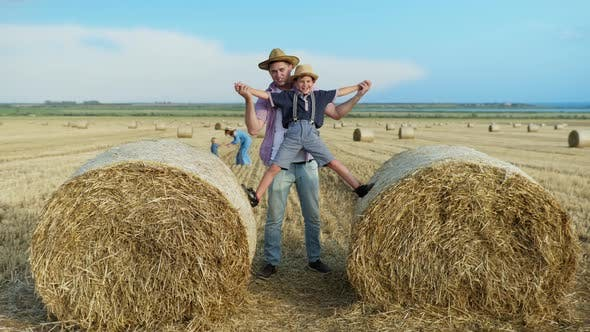Parenting Pleasures, Father Spends Time Playing with Baby on Straw Bales in Field