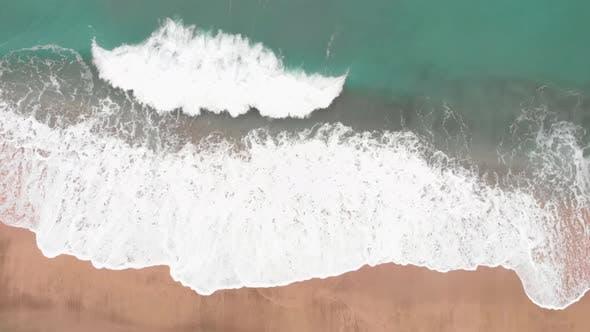 Powerful stormy blue sea waves crashing on sandy beach
