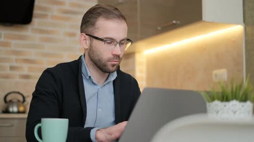 Remote Job. A Man Is Working with Documents on Laptop Remotely at Home. A Business Man Is Using