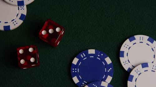 Rotating shot of poker cards and poker chips on a green felt surface - POKER 020