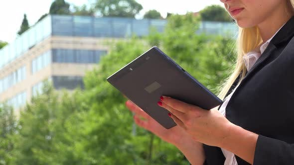 Cover Image for A Businesswoman Works on a Tablet - Closeup - an Office Building in the Blurry Background