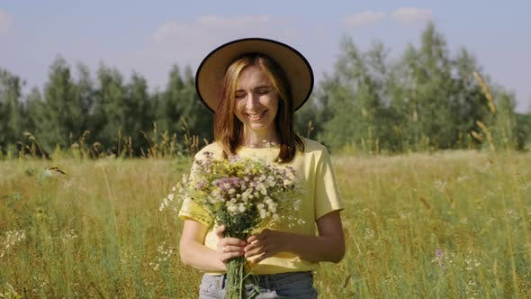 Portrait of Smiling Beautiful Woman in Hat with Bouquet of Wildflowers