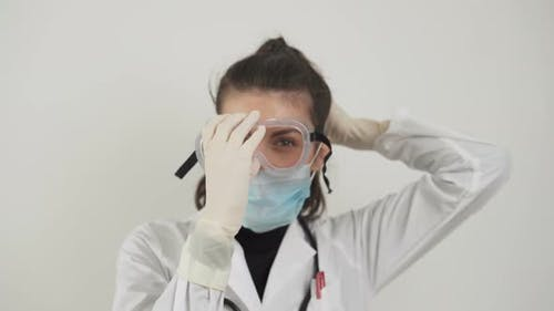 Young Female Doctor Puts Protective Plastic Glasses and Facemask Against Coronavirus