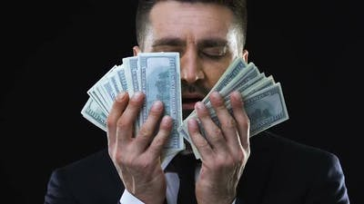 Greedy Business Man Stroking Face With Dollars Banknotes, Enjoying Wealth