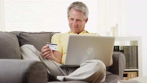 Senior man with laptop buying online
