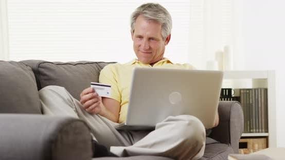 Thumbnail for Senior man with laptop buying online