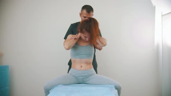 Thumbnail for Chiropraktische Behandlung - der Arzt bewegt den Körper der jungen Frau zu den Seiten