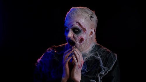Frightening Man with Halloween Zombie Undead Bloody Wounded Face Makeup Scared By Police Ligths
