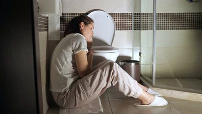Young Woman Sitting Near Toilet