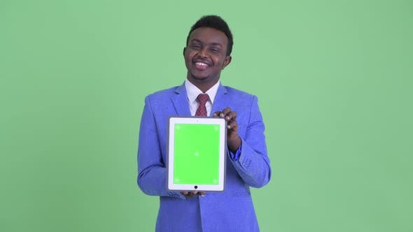Thumbnail for Happy Young African Businessman Thinking While Showing Digital Tablet