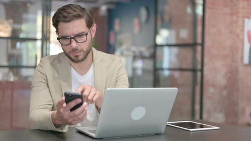 Young Man with Laptop Using Smartphone