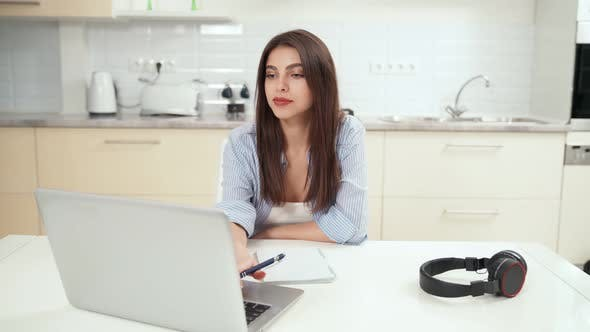 Smiling Young Woman Studying or Working Online at Home