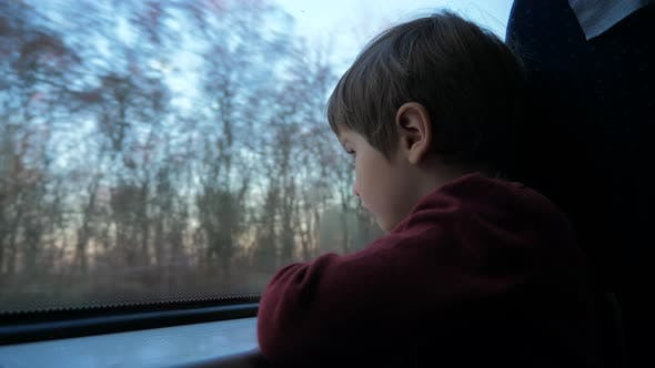 Thumbnail for Close-up shot of a little curious boy looking out of the window in train. Its raining outside.