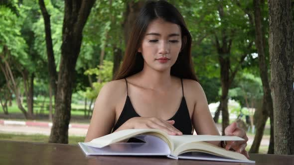 Beautiful woman reading knowledge from a book