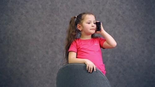 Positive little girl talking on the phone