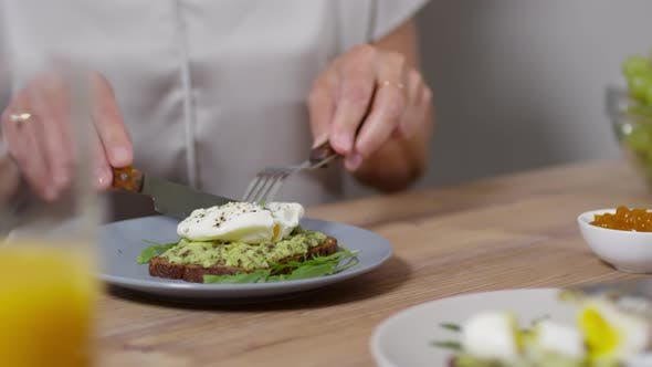 Unrecognizable Woman Cutting Poached Egg with Runny Yolk on Toast