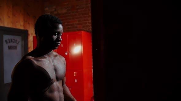 Thumbnail for Afroamerikanischer athletischer junger Mann steht im Umkleideraum