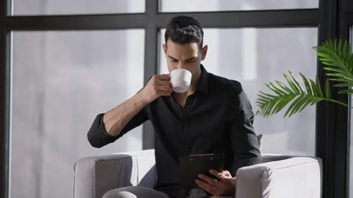 Professional Middle Eastern Male Expert Drinking Morning Coffee Sitting at Sunny Window in Home