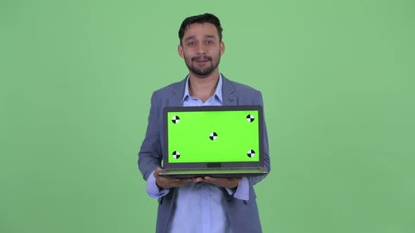 Thumbnail for Happy Young Bearded Persian Businessman Talking While Showing Laptop