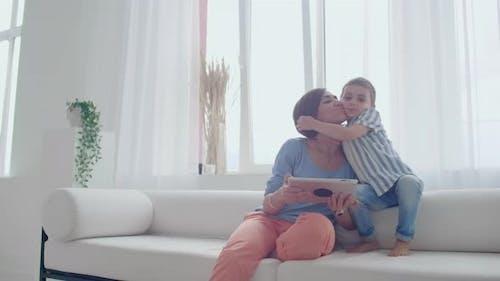 Mutter und Sohn spielen zu Hause mit digitalem Tablet