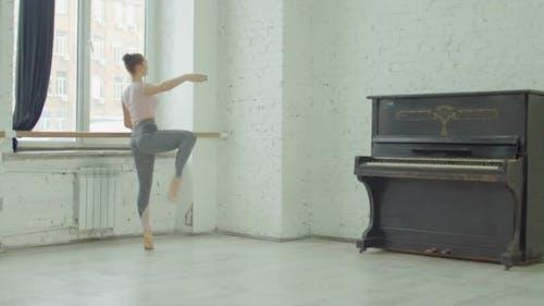 Ballerina Performing Dedans Exercise at Barre