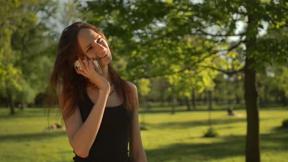 Thumbnail for Smiling Young Woman Stand at the Park Outdoors Talk By Phone