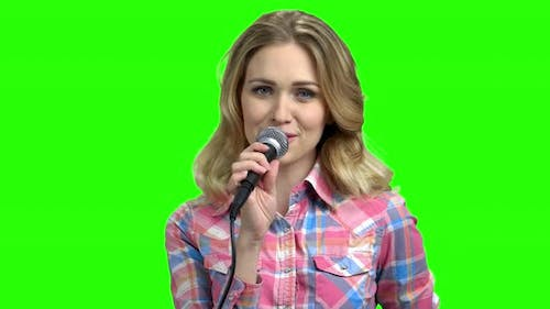 Young Woman in Casual Wear Singing in Microphone