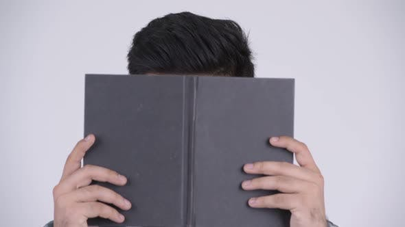 Thumbnail for Young Indian Nerd Man Covering Face with Book