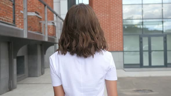 Thumbnail for Walking Young Female Designer, Back View, Outside Loft Office